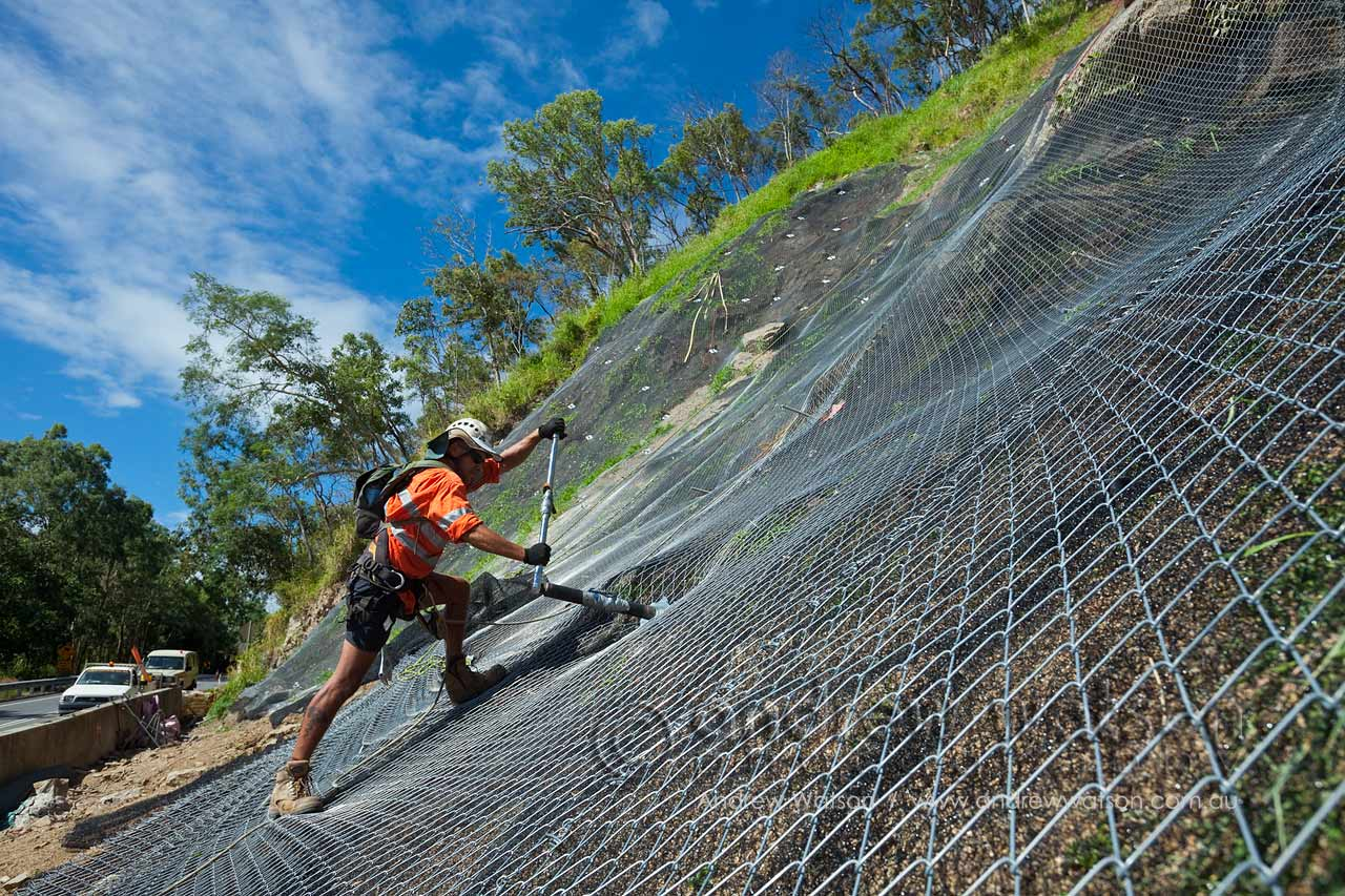 Worker tightening an anchor bolt holding the mesh to the hillside
