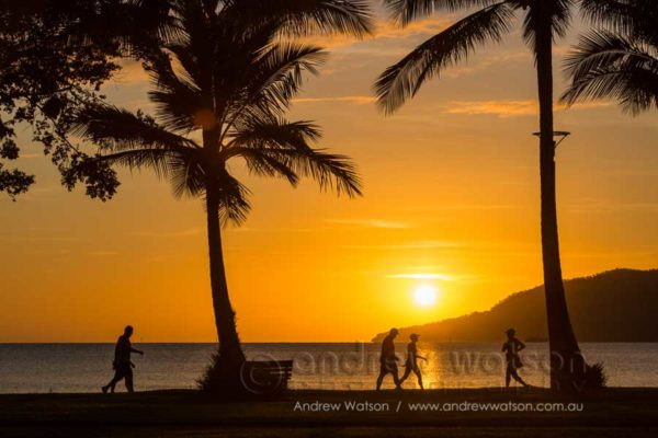 Walkers along the Cairns Esplanade at dawn