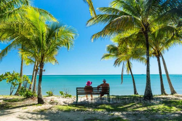 Couple relaxing amidst the coconut palms of Clifton Beach, Cairns