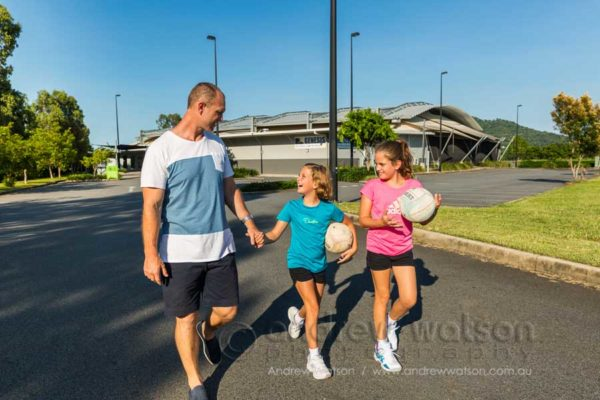 Lifestyle image of a father and kids outside sports centre
