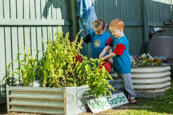 Children watering plants in garden at Pelican Childcare