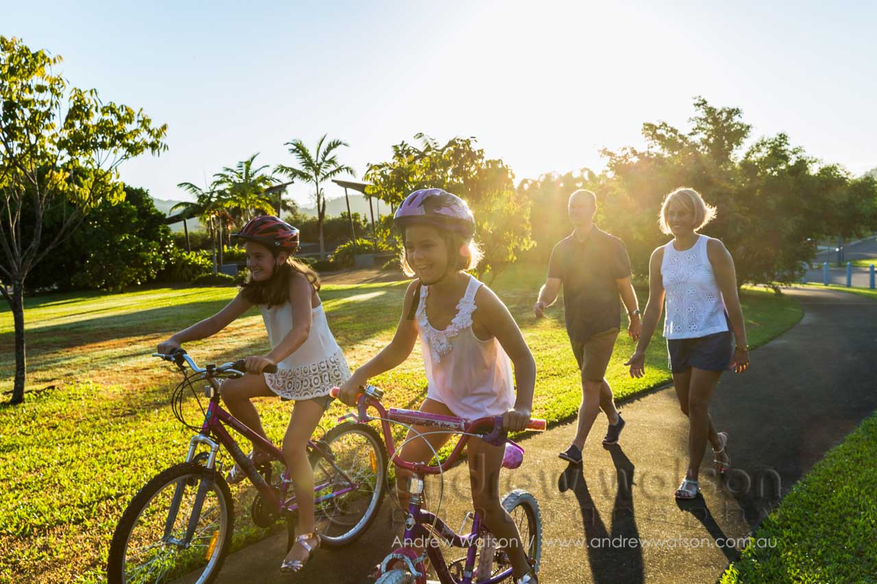 Lifestyle image of kids cycling through park with parents