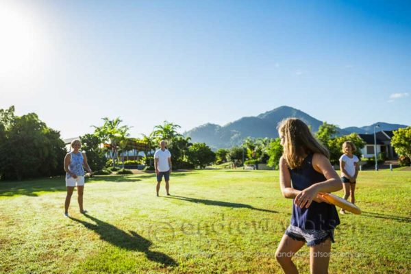 Lifestyle image of young family playing frisbee in park