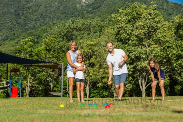 Lifestyle image of young family playing bocce in park