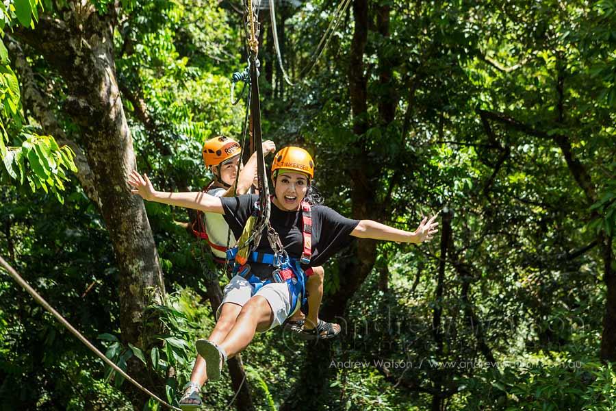 Couple having fun moving between platforms on rainforest canopy zipline