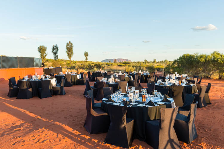 Image of an outdoor restaurant with Uluru in the distance