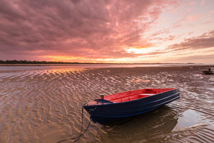 Image of dinghy on the shores of Sunset Bay beach at low tide