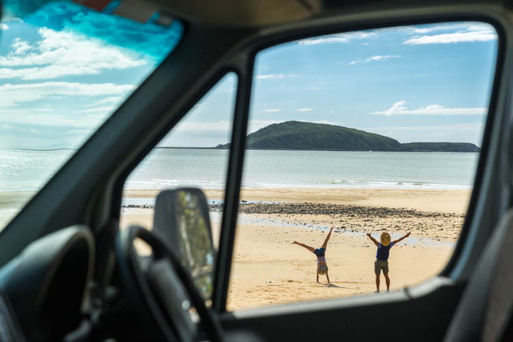 Image of couple on Shoal Point beach from car window, Mackay