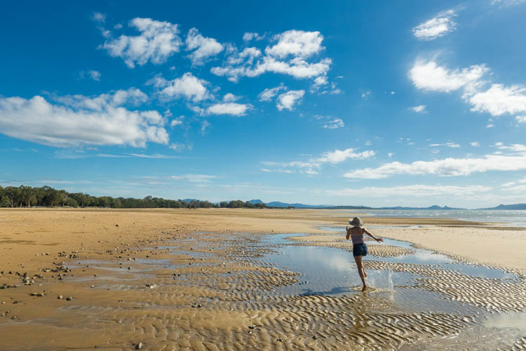 Image of woman running along Shoal Point beach, Mackay