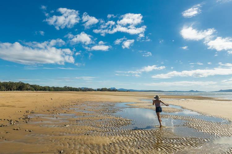 Image of woman running along Shoal Point beach, Mackay