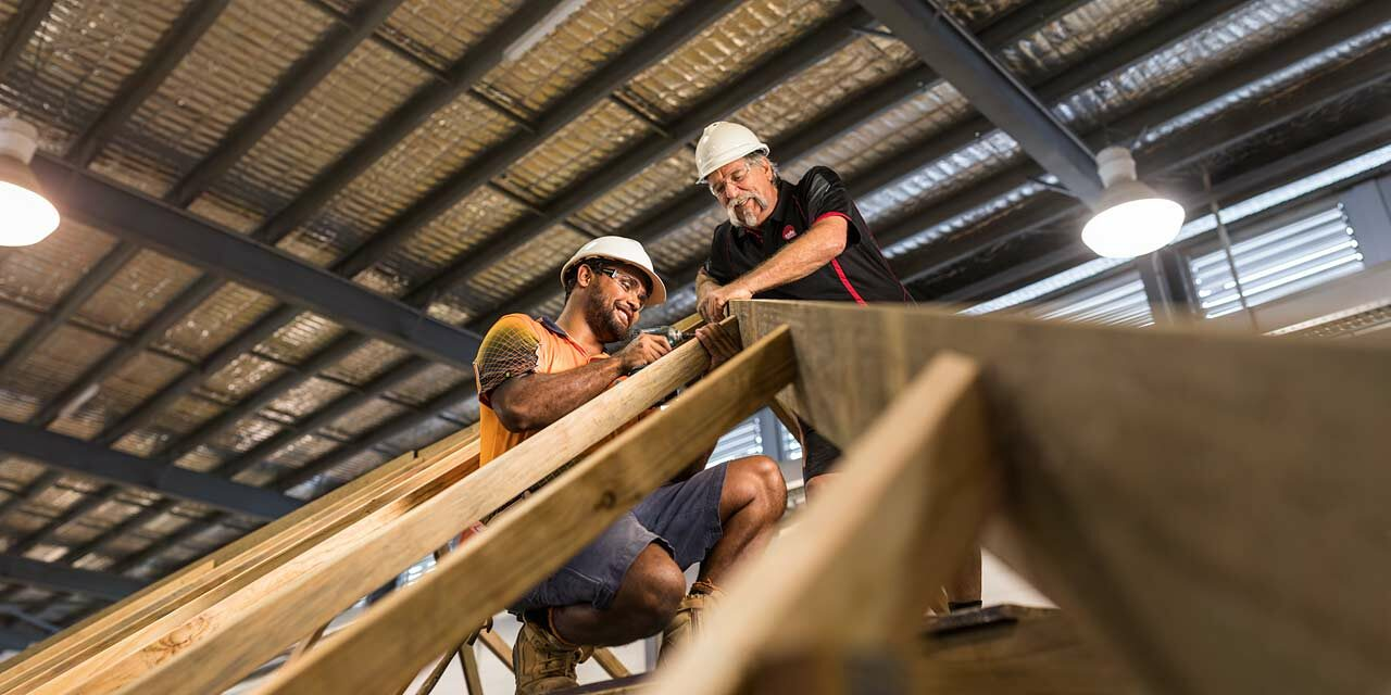 Construction student building a roofing frame with his teacher watching on