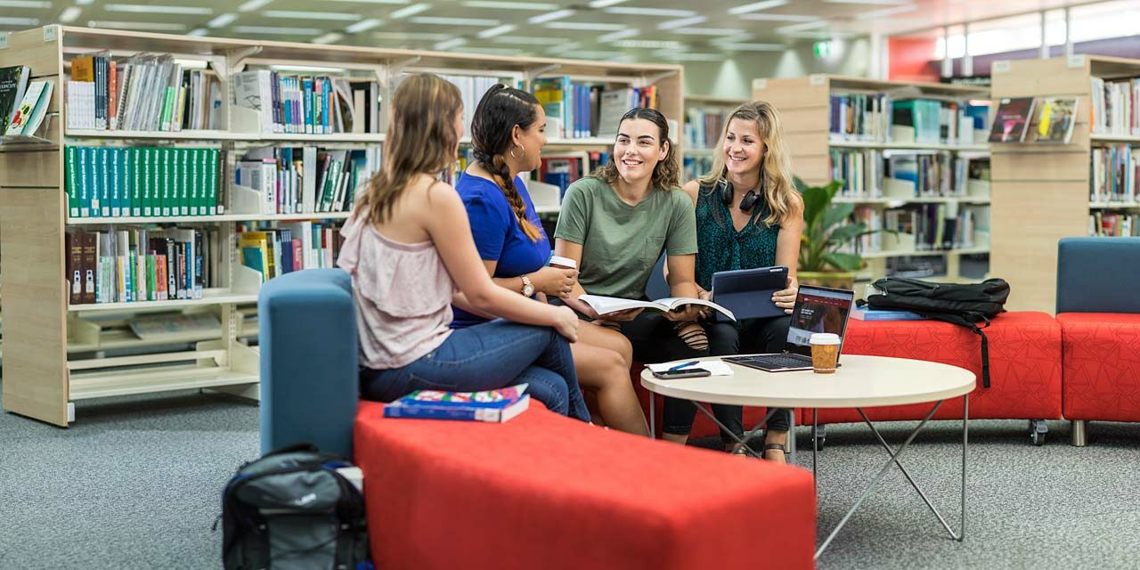 A group of TAFE students discussing a project whilst sitting in the library