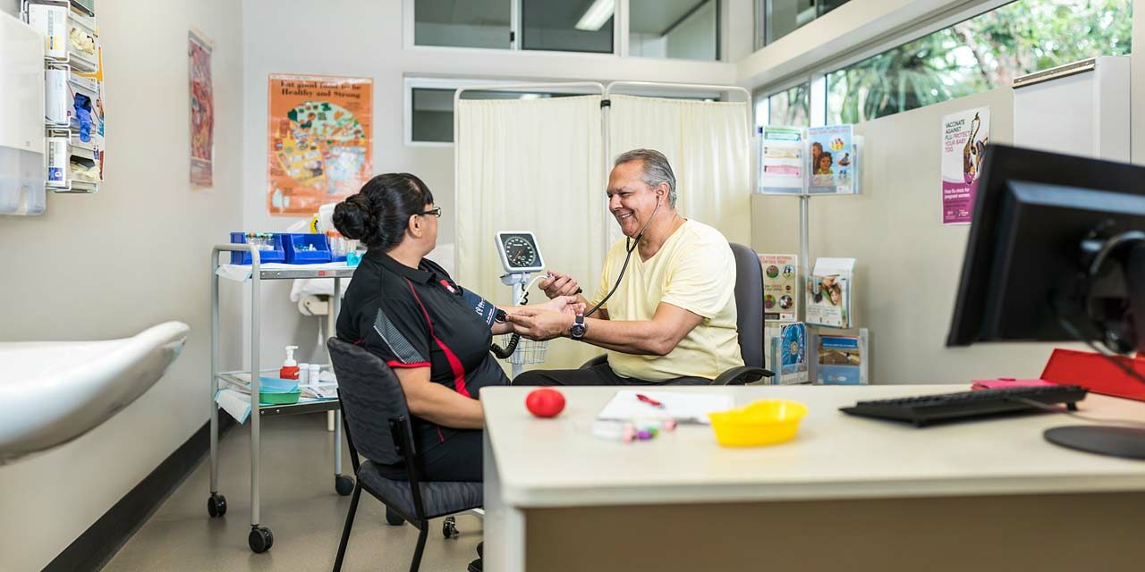 A healthcare student taking the blood pressure of his teacher