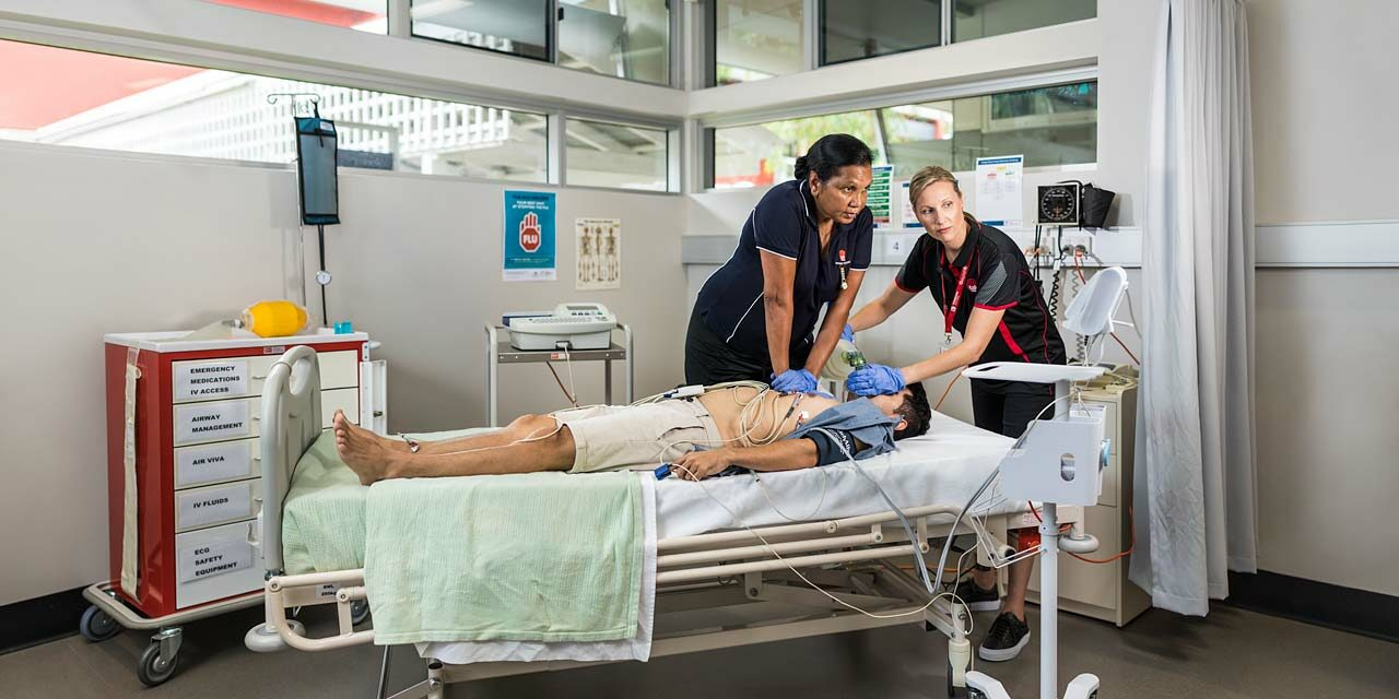 Nursing student practicing CPR on patient with teacher assisting