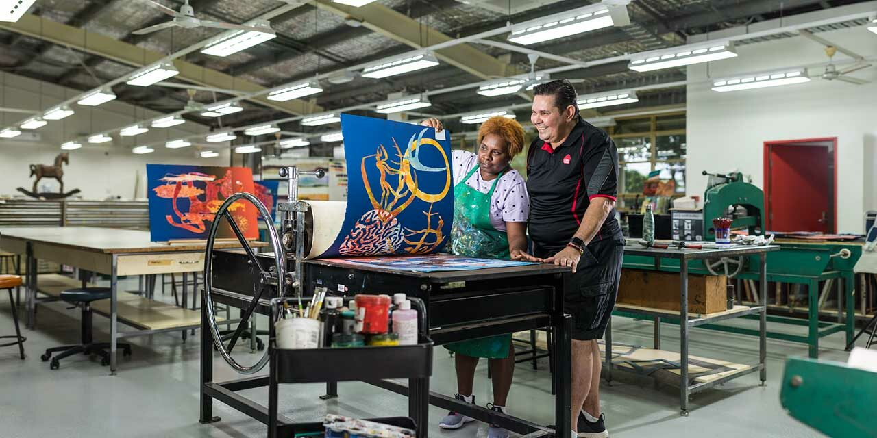 Indigenous arts student looking at artwork on printing press with teacher looking on