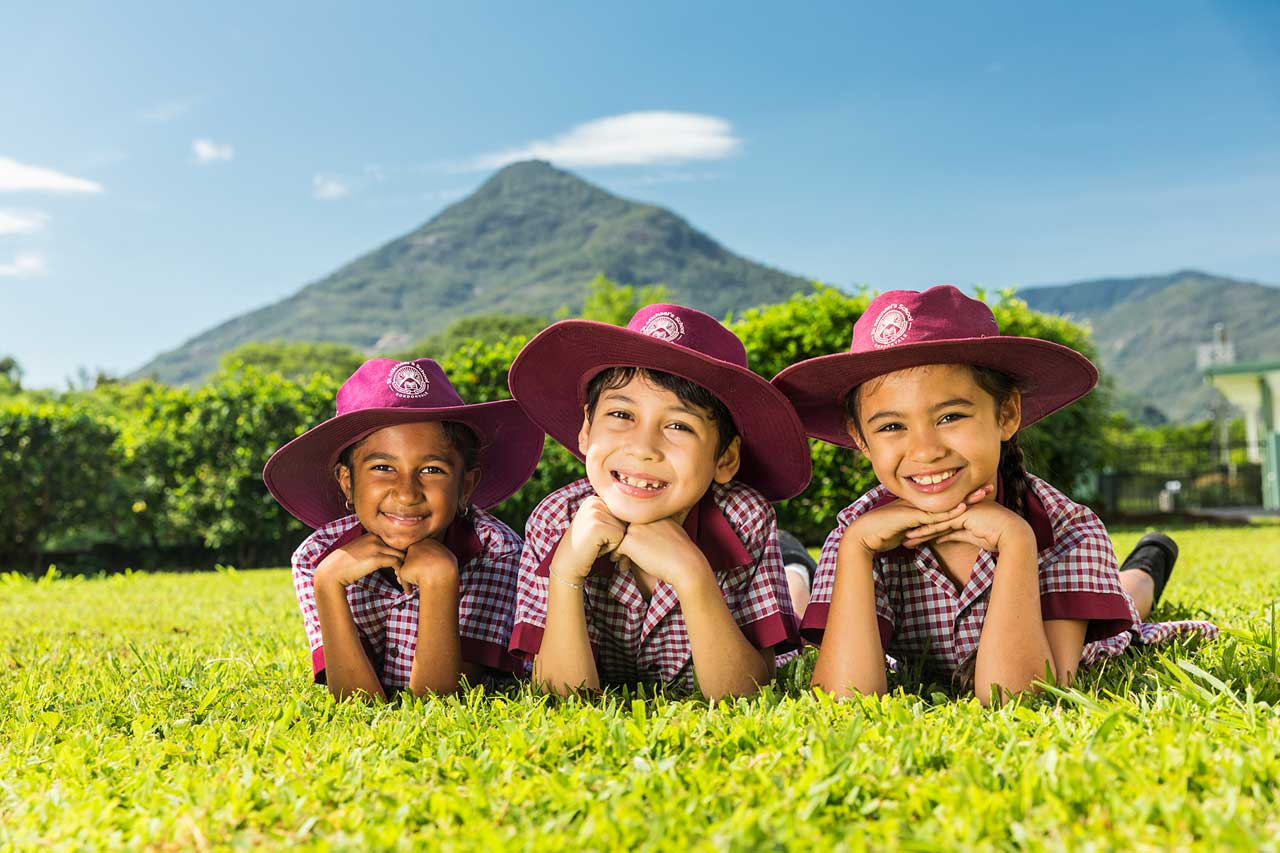 Portrait of three young students of different ethnicities laying on grass smiling