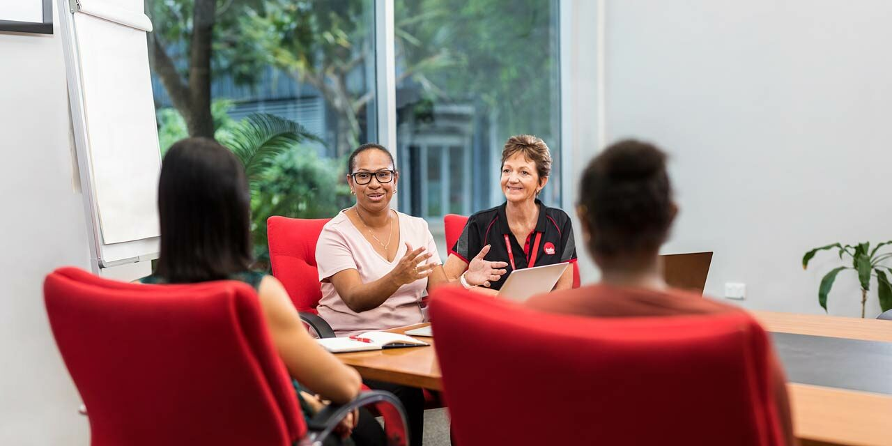Indigenous business student presenting at a meeting with teacher looking on