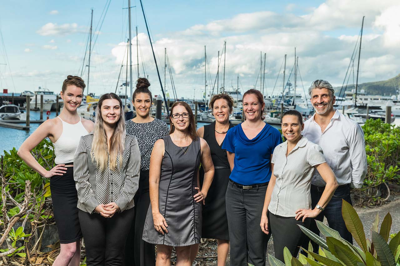 Group photo of an accounting firm staff members with harbour background