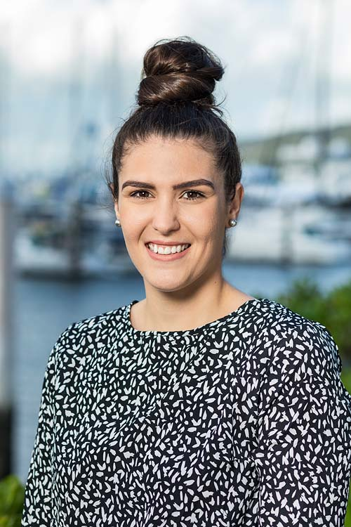 Corporate headshot of a female accountant with harbour background