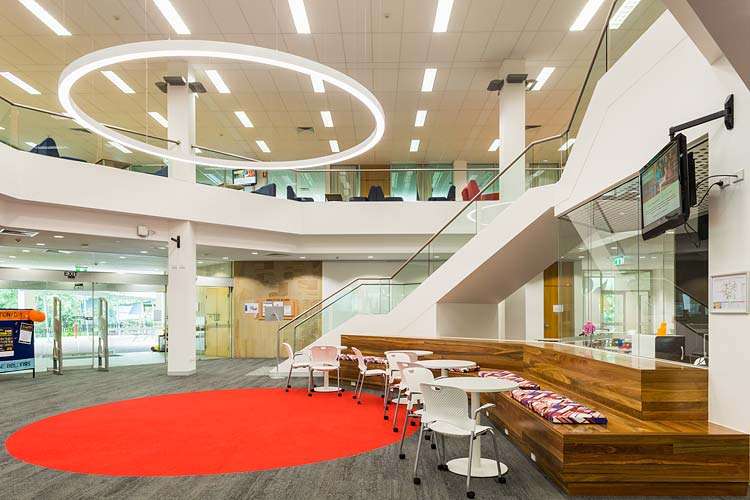 Interior of the James Cook University library showing entry seating and circular lighting