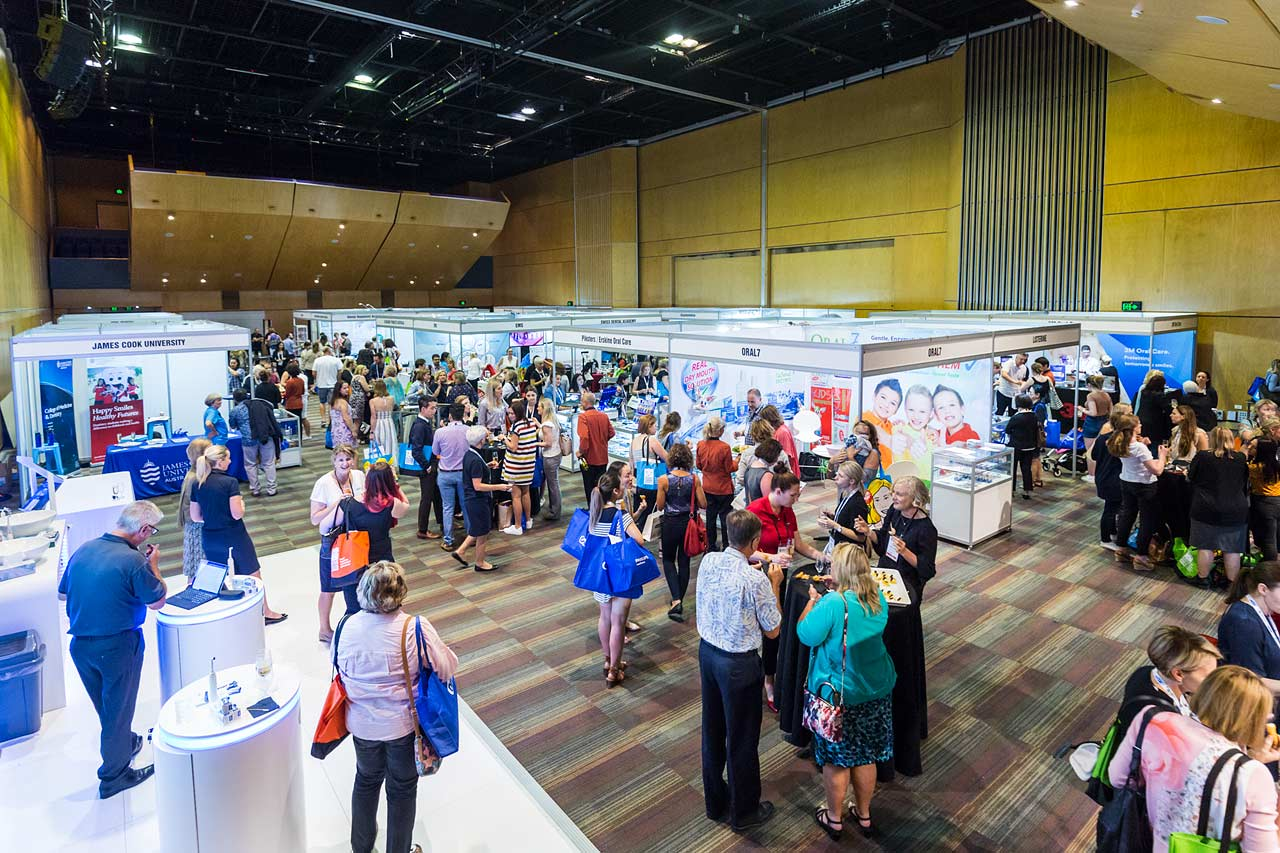 View of delegates and supplier booths at dental symposium trade exhibition